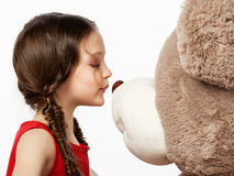 Portrait of a little brunette girl kissing a teddy bear into it' Royalty Free Stock Images