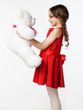 Portrait of a little brunette girl in a red dress with a soft be Royalty Free Stock Images