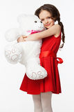 Portrait of a little brunette girl with a soft bear toy Royalty Free Stock Photos