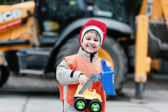 Portrait of little builder in hardhats working outdoors near Tractor excavator. Royalty Free Stock Photo