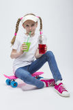 Portrait of Little Caucasian Blond Girl in Visor Sitting on Pink Pennyboard With Two Cups of Juice and Drinking Stock Image