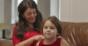 Portrait of little Caucasian brunette girl looking at camera and smiling. Mother tying her lovely daughter ponytail at stock video footage
