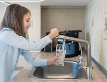 Portrait of a little caucasian girl gaining a glass of tap clean water. Kitchen faucet. Cute curly kid pouring fresh water from
