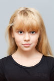 Portrait of little Caucasian ordinary girl. Closeup studio face portrait of little Caucasian ordinary girl  on gray background Royalty Free Stock Images