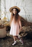 Little lovely kid in peachy dress and hat posing at camera. royalty free stock images
