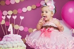 Portrait of a little cheerful birthday girl with the first cake. Eating the first cake. Smash cake.  stock photography