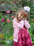 Portrait of the little cheerful girl in a garden stock images