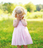 Portrait of little child closes her face outdoors Stock Photos