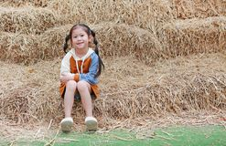 Portrait of little child girl and warm clothes sitting on pile of straw on a winter season royalty free stock photo