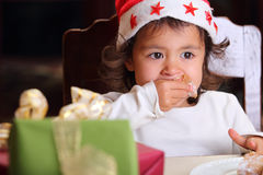 Portrait of little child with intense gaze. Adorable little child has intense gaze while eating a piece of a Christmas cake . The child wears a xmas hat Royalty Free Stock Photos