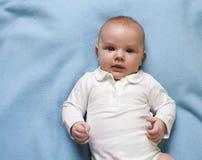 Portrait of a little child lying on  blue blanket Stock Photo