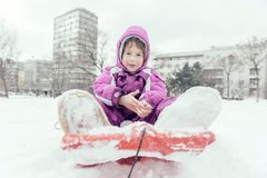 Portrait of the little child outdoor. Little girl sitting on the sled,selective focus Stock Image