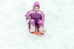 Portrait of the little child outdoor. Little girl sliding outdoor in the snow,selective focus Stock Photo