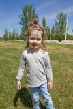 Portrait of little child with pigtail in park. Funny portrait of blonde three years old child with pigtail, grey shirt and blue jeans trousers, standing in green Stock Image