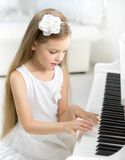 Portrait of little child in white dress playing piano Royalty Free Stock Images