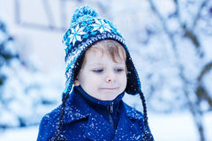 Portrait of little child in winter clothes with falling snow Stock Photos