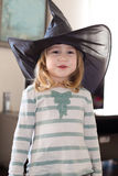 Portrait of little child with witch hat. Portrait of three years old blonde child with white and green shirt with black big witch hat, looking and smiling Stock Photo