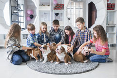 Portrait of little children with cute puppies on the floor at home Stock Photo