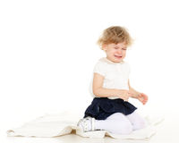 Portrait of little crying  girl. Unhappy crying little child sits on the floor on a white background Stock Image