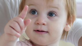 Portrait of little curious female child with beautiful big gray eyes points finger closeup