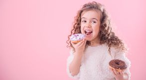 Portrait of a little curly girl eating donuts. Portrait of a little joyful cute curly girl who eats donuts, on a pink background, a place for text stock photography