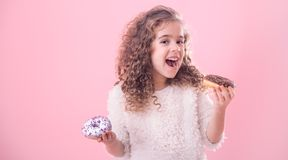 Portrait of a little curly girl eating donuts. Portrait of a little joyful cute curly girl who eats donuts, on a pink background, a place for text stock photos