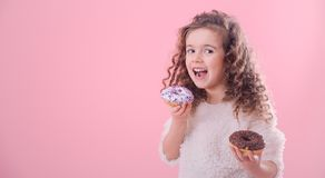 Portrait of a little curly girl eating donuts. Portrait of a little joyful cute curly girl who eats donuts, on a pink background, a place for text stock image
