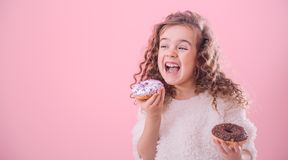 Portrait of a little curly girl eating donuts. Portrait of a little joyful cute curly girl who eats donuts, on a pink background, a place for text royalty free stock photo
