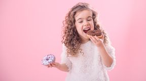 Portrait of a little curly girl eating donuts royalty free stock image