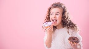 Portrait of a little curly girl eating donuts stock photos