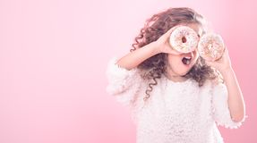 Portrait of a girl with an open mouth and donuts. Portrait of a little curly girl with an open mouth and donuts in her hands, closes her eyes with donuts, on a royalty free stock photo
