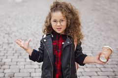 Portrait of little curly hipster girl in glasses with coffee. Urban style. Autumn Stock Photography