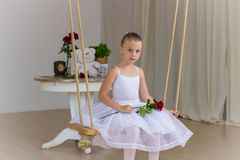 Portrait of little cute ballerina on swing. Royalty Free Stock Image