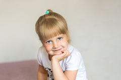 A portrait of little cute blonde caucasian girl sitting on a bed with purple cover. She holds her head by hand. Girl has big beaut Royalty Free Stock Photos