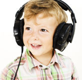 Portrait of little cute boy in big earphones happy smiling isolated on white background, lifestyle people concept Royalty Free Stock Image