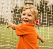 Portrait of little cute boy on football field Stock Photos