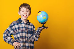 Portrait of little cute boy with globe. Isolated over yellow background. royalty free stock images
