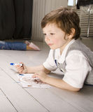 Portrait of little cute boy painting on floor Royalty Free Stock Photo