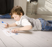 Portrait of little cute boy painting on floor Stock Photo