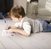 Portrait of little cute boy painting on floor Stock Image