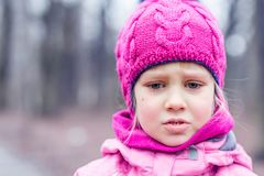 Portrait of little cute caucasian girl in pink knitted hat crying , being upset or lost in a forest or city park stock photo