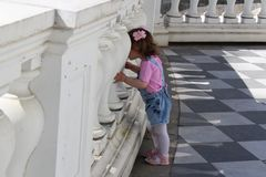 Little girl walks in the park and looks through the biton fence stock image