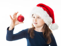 Portrait of a little cute Christmas girl. Portrait of a little cute girl wearing a Christmas Hat, holding a red Christmas ball, looking away from the camera Royalty Free Stock Photography
