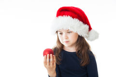 Portrait of a little cute Christmas girl. Portrait of a little cute girl wearing a Christmas Hat, holding a red Christmas ball, looking away from the camera Stock Photography
