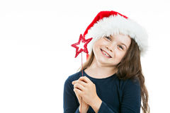 Portrait of a little cute Christmas girl. Portrait of a little girl wearing a Christmas Hat, holding a red star. Isolated on white background Stock Photography