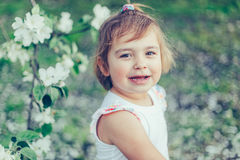 Portrait of little cute disheveled girl laughing and having fun outdoors among flowering trees in a sunny summer day Royalty Free Stock Image