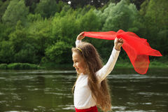 Portrait of little cute girl dance with red Scarf by the river Stock Photo