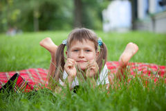 Portrait of little cute girl lies green grass Stock Images