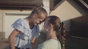 Portrait little cute girl and mother standing in the backyard outdoors. Relationship mom and daughter. Real happy family. The little cute girl kissing her mother stock video footage