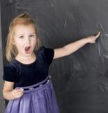 Portrait of little cute girl near blackboard Stock Photo